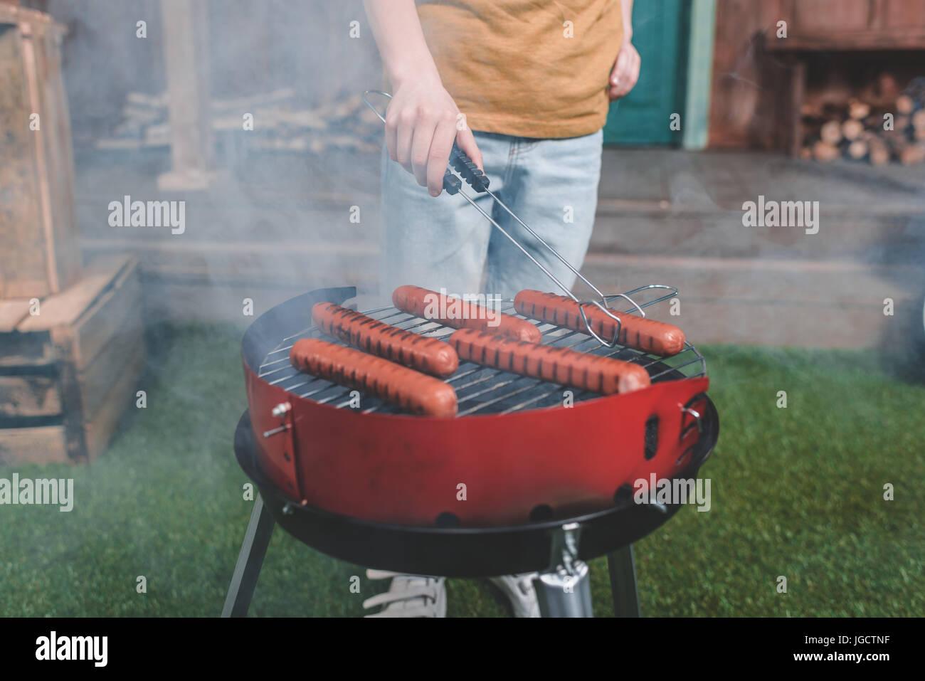 Vue partielle de la cuisson des saucisses hot-dog boy sur grill Photo Stock