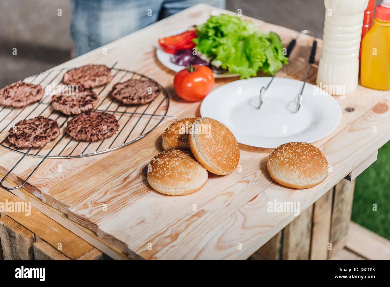 Vue en gros plan de divers ingrédients burgers sur table en bois Photo Stock