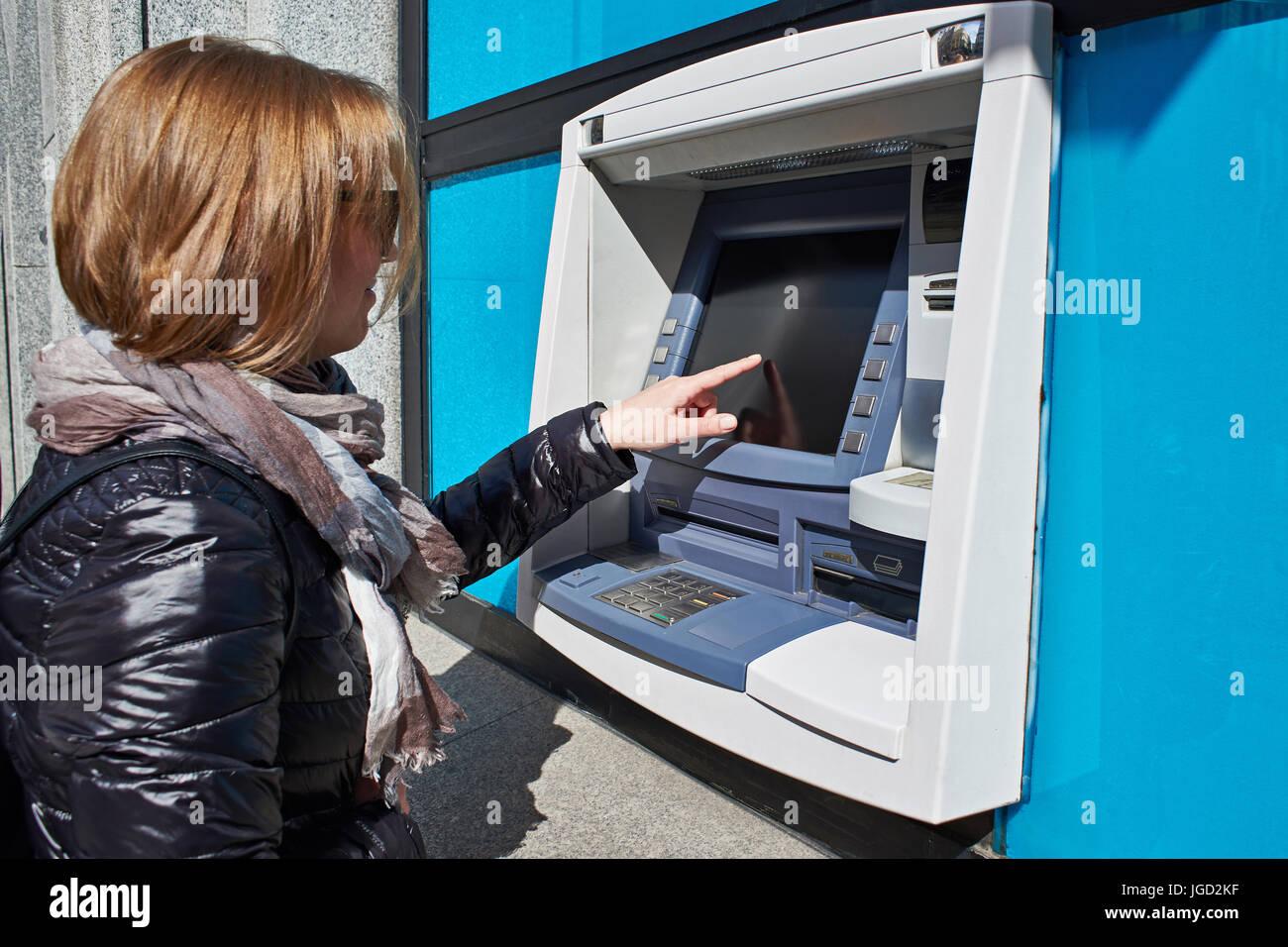 Sur l'écran tactile femme utilise un distributeur automatique Photo Stock