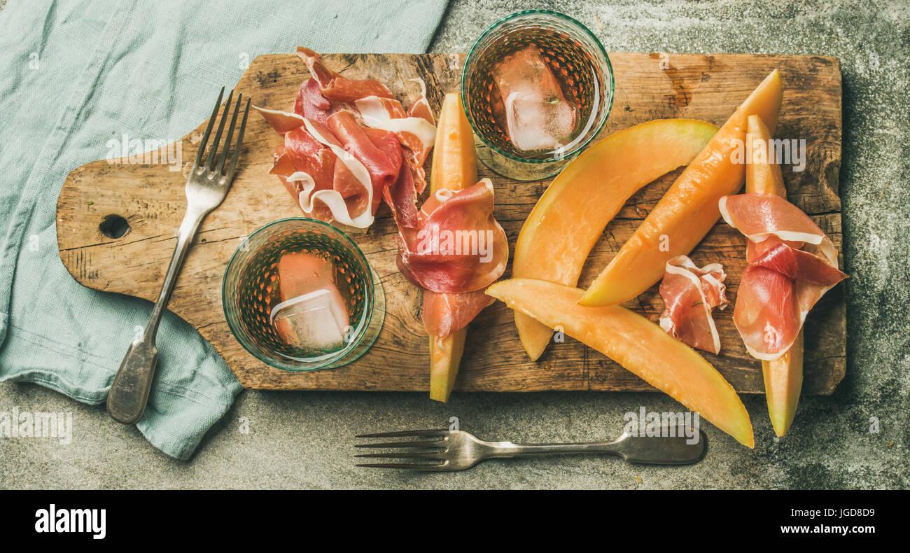 Flatlay de vin rose, du jambon prosciutto, melon, vue d'en haut Banque D'Images