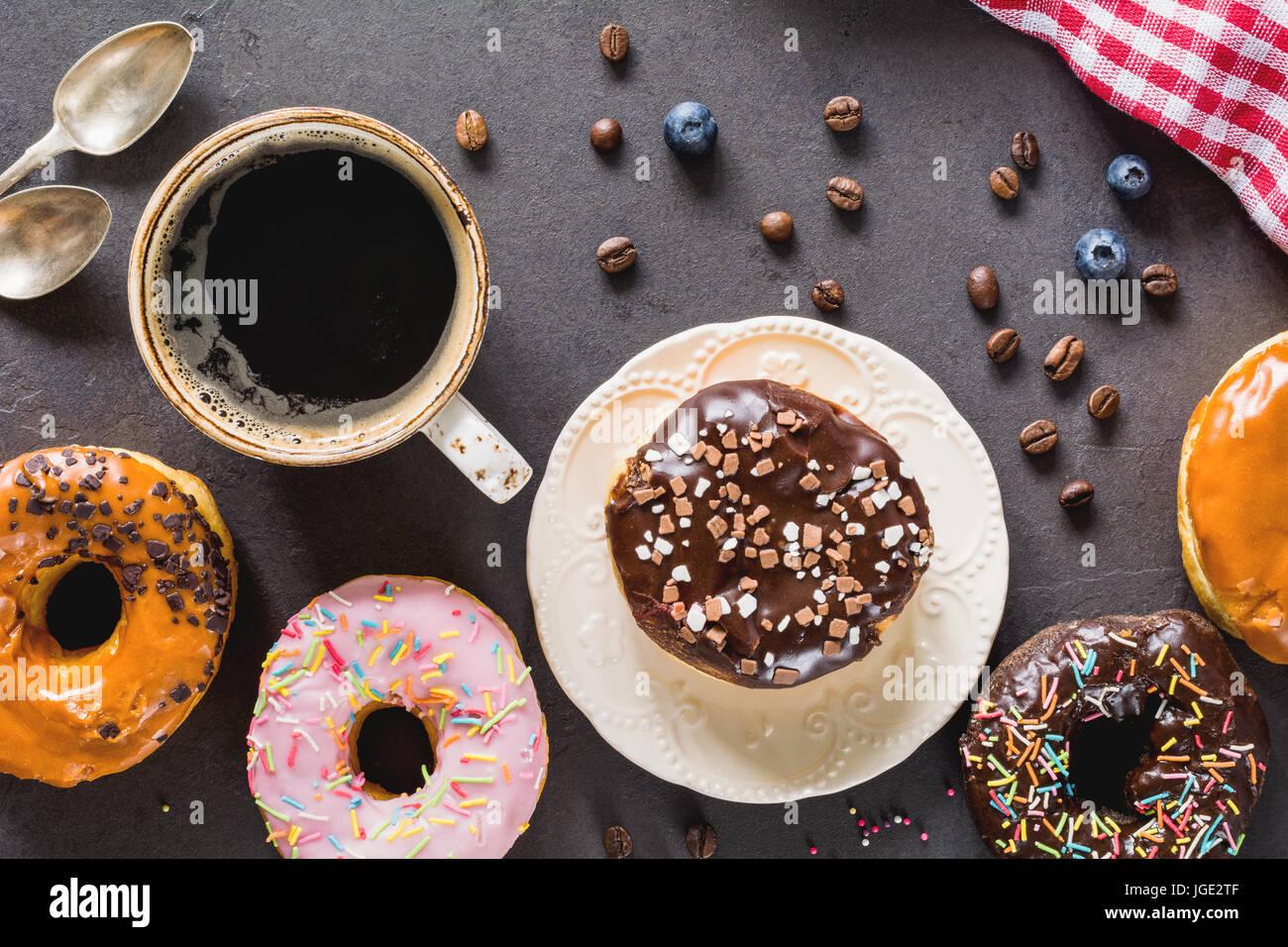 Les beignes glacés et tasse de café espresso noir sur fond de pierre. Vue d'en haut. Mise à plat Photo Stock