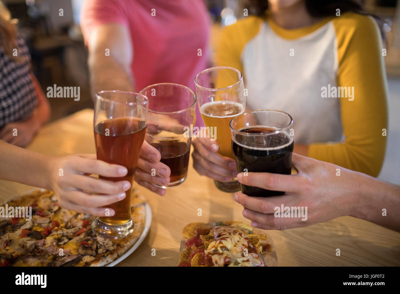 Les mains coupées de friends toasting drinks at table in restaurant Photo Stock
