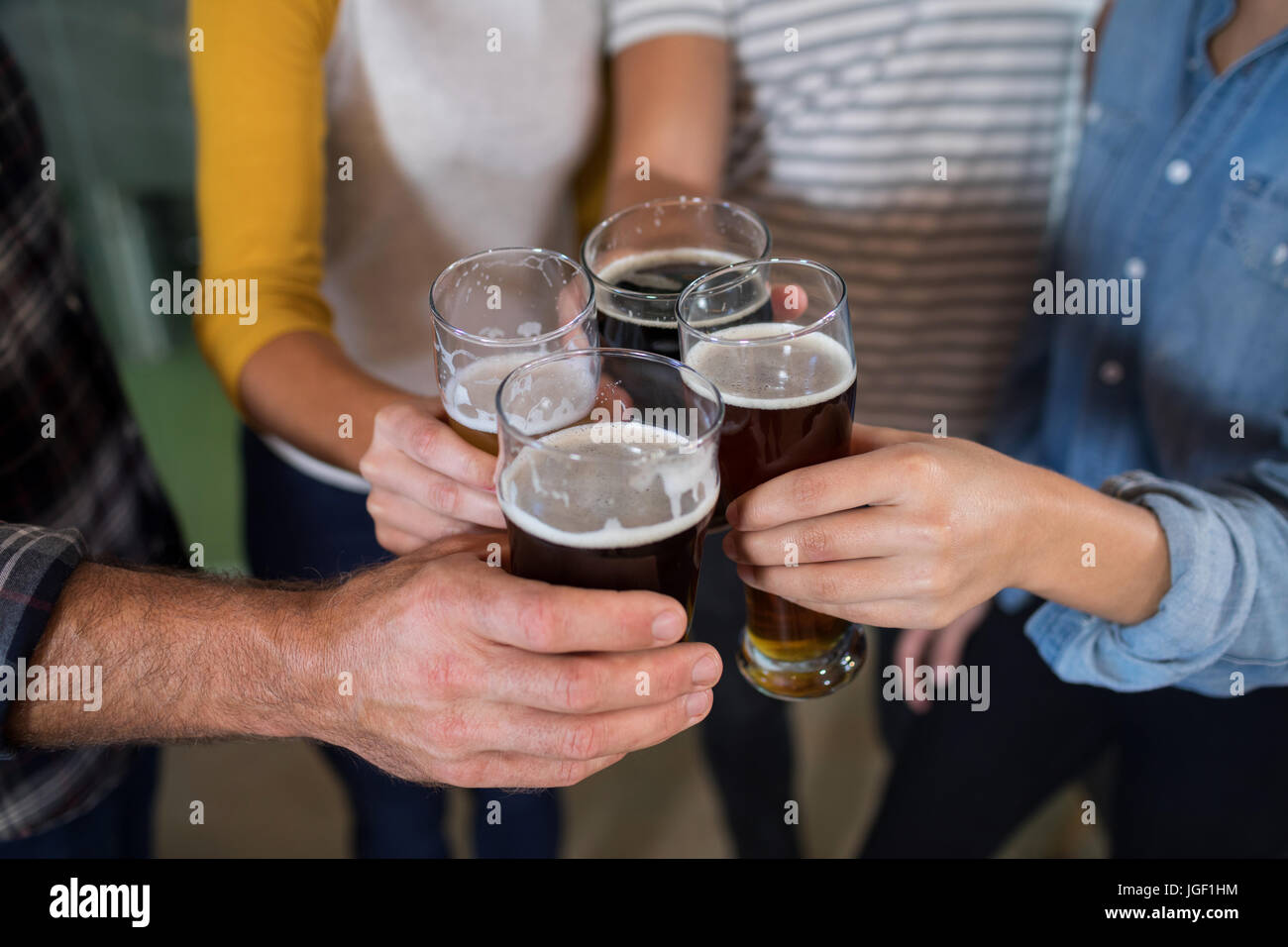 Les mains coupées de friends toasting drinks à l'usine Photo Stock