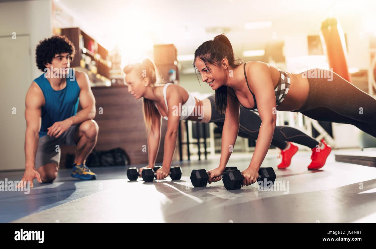 Deux jeune fille souriante de l'exercice à la salle de sport avec un entraîneur personnel. Photo Stock