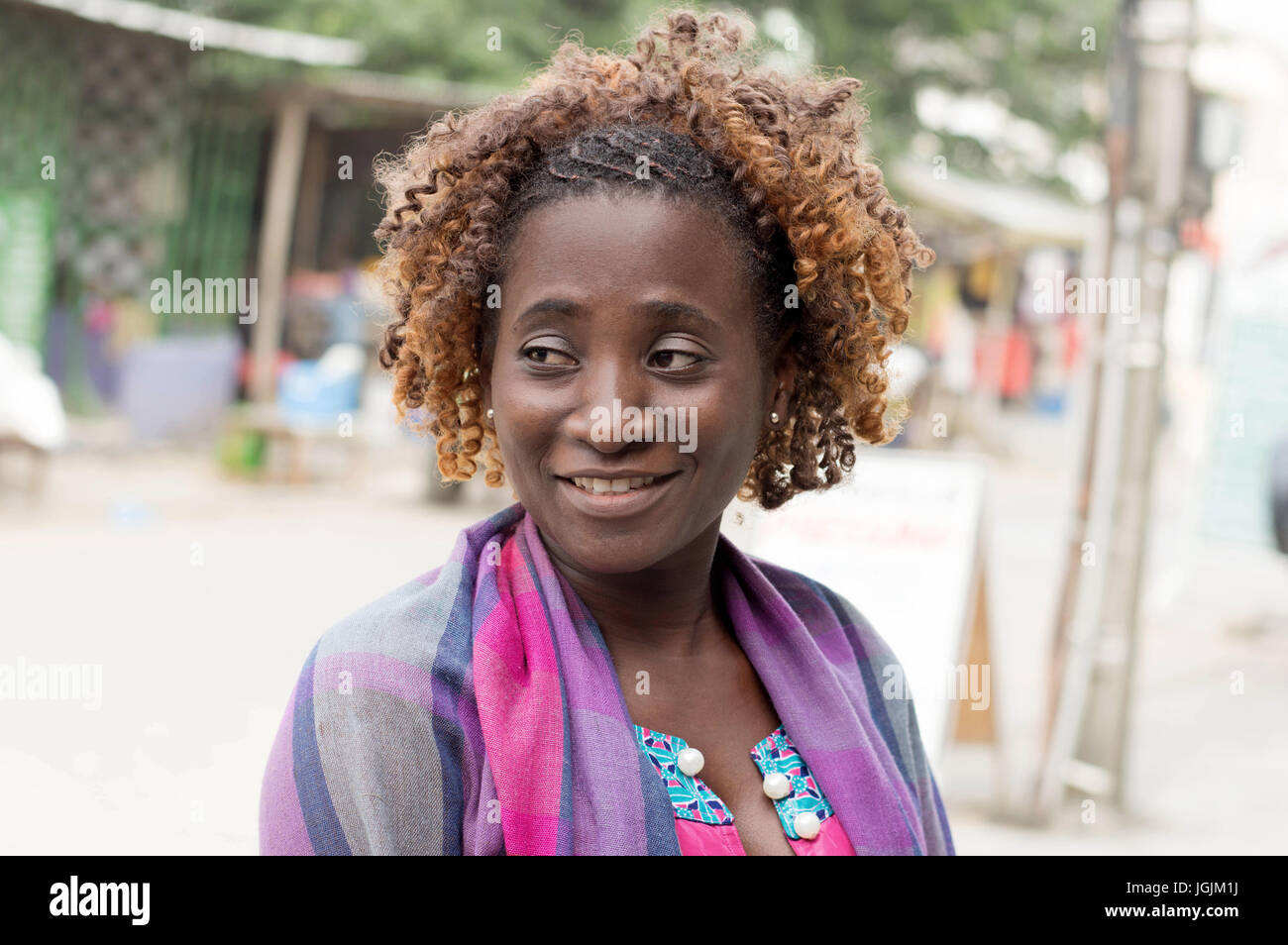 Souriante jeune femme se tient debout au bord de la route chercher ailleurs. Photo Stock