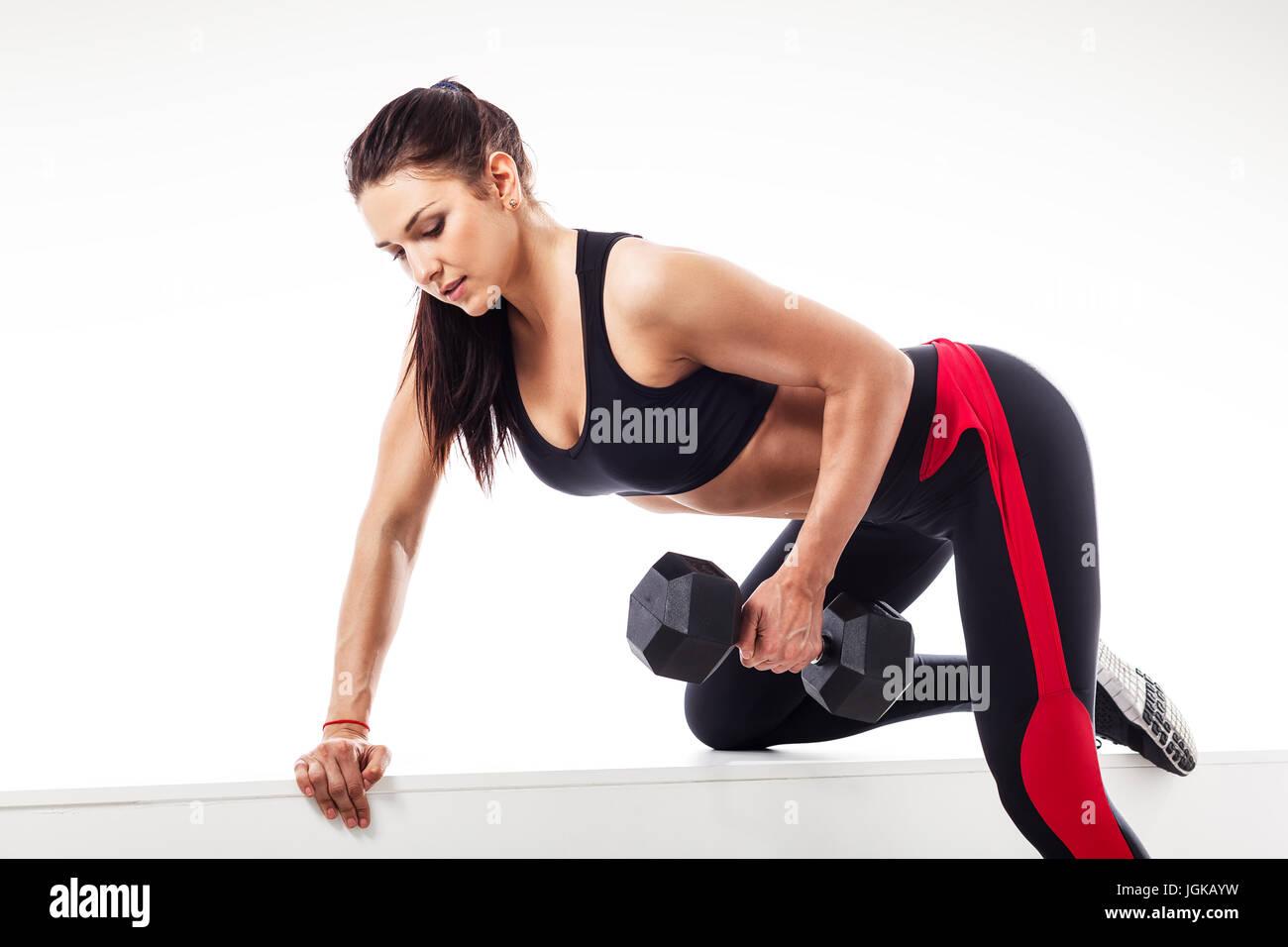 Jeune femme brune athlétique de faire un exercice avec un haltère sur le  biceps s appuyant sur un banc de sport sur un fond isolé blanc c6f3e72aafc