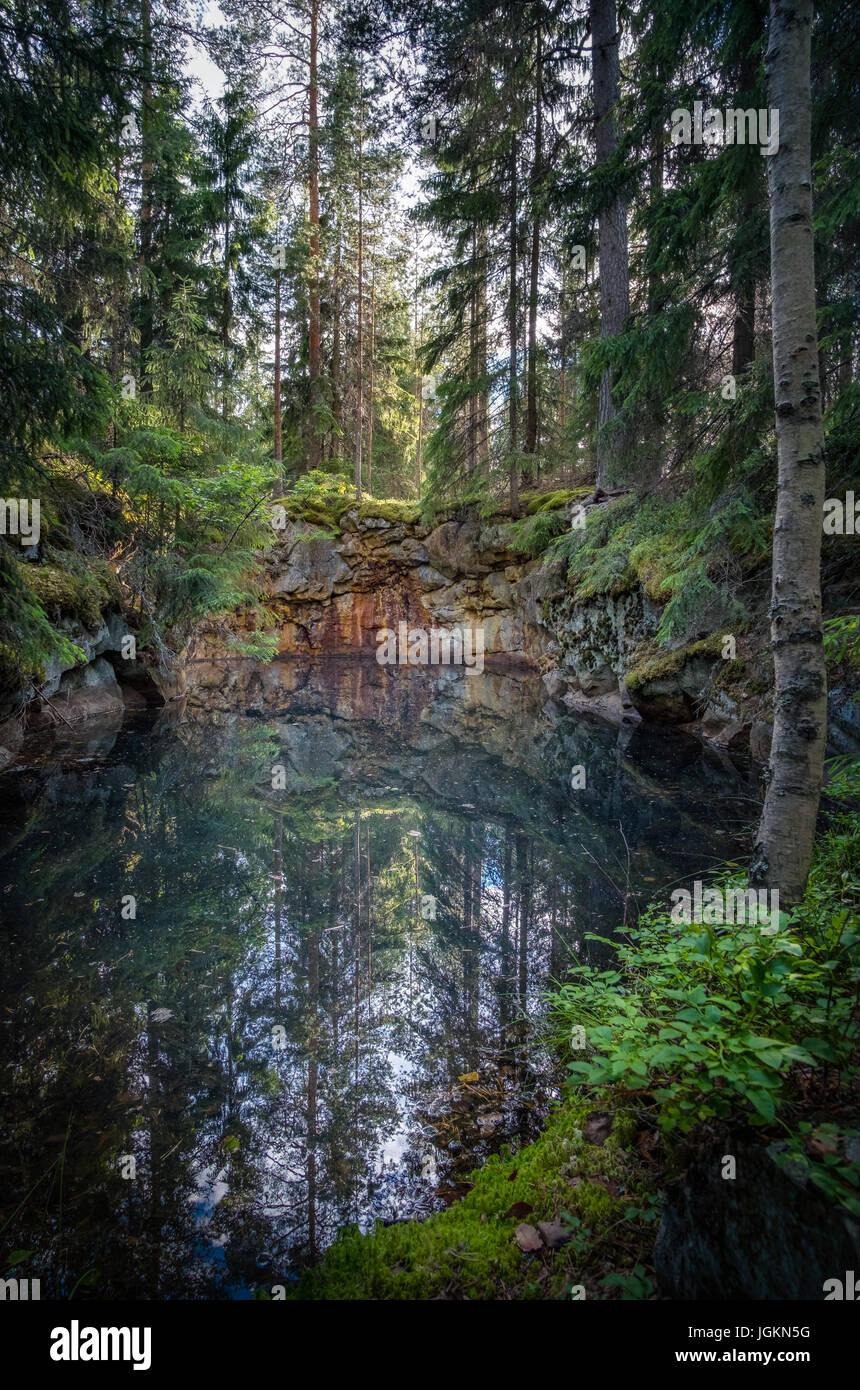 Ancien et historique plein de mine avec de l'eau couleur jade verdâtre au milieu de la forêt. Cette Photo Stock
