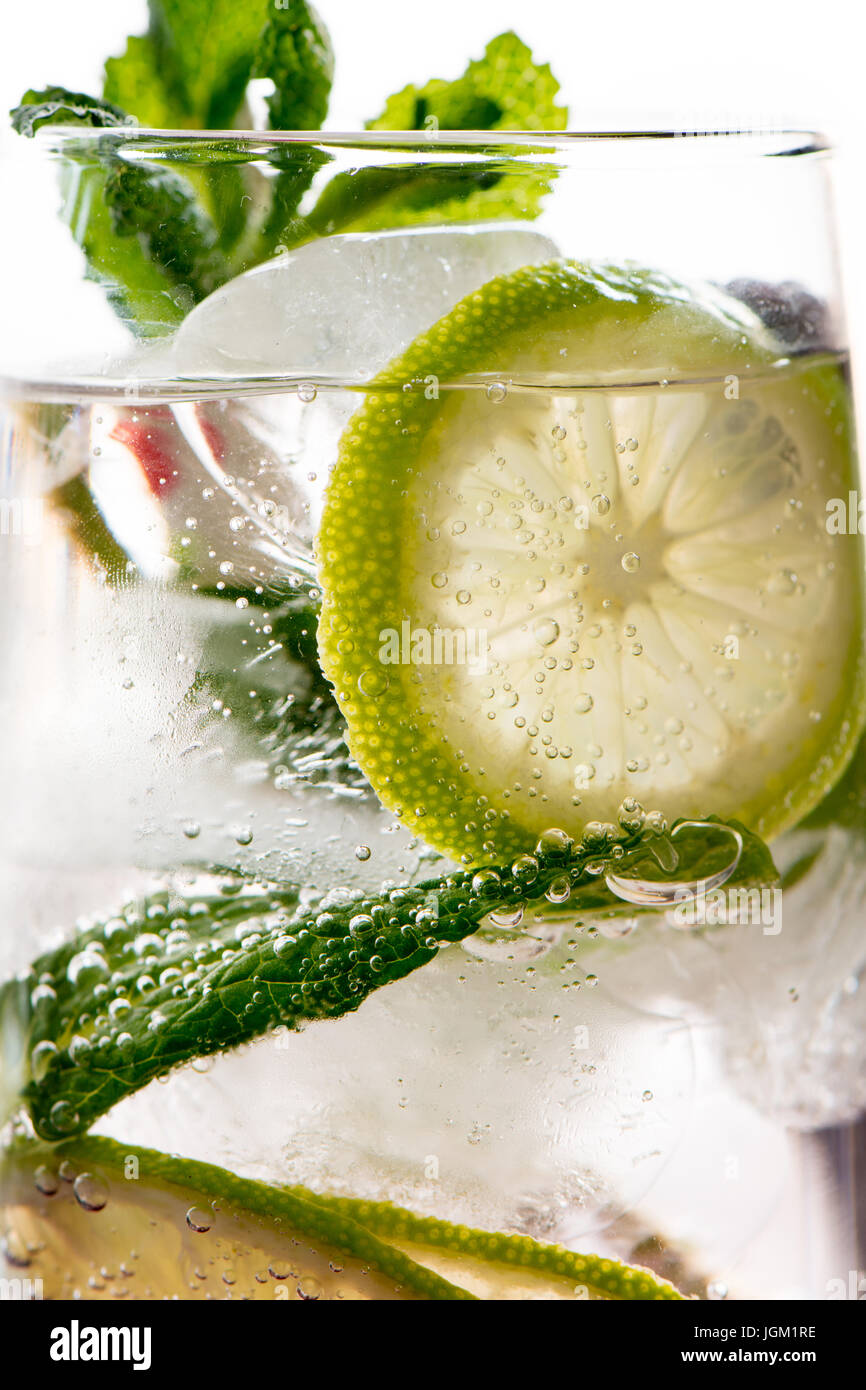 Cocktail gin tonic avec de la chaux, de la glace au citron et menthe, fond blanc. Close up detail Photo Stock
