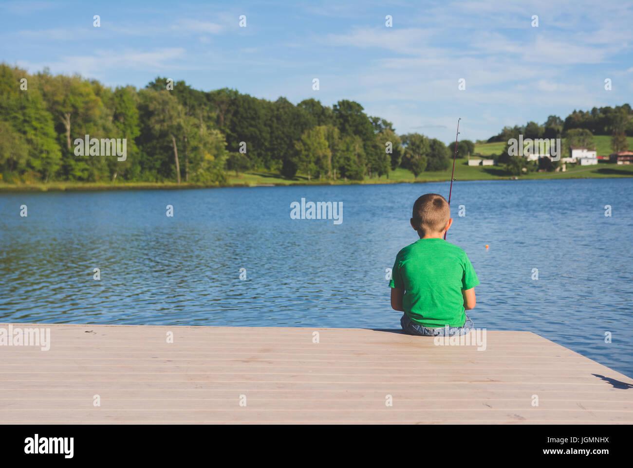Un enfant sur un quai de pêche à un étang dans une zone rurale. Photo Stock