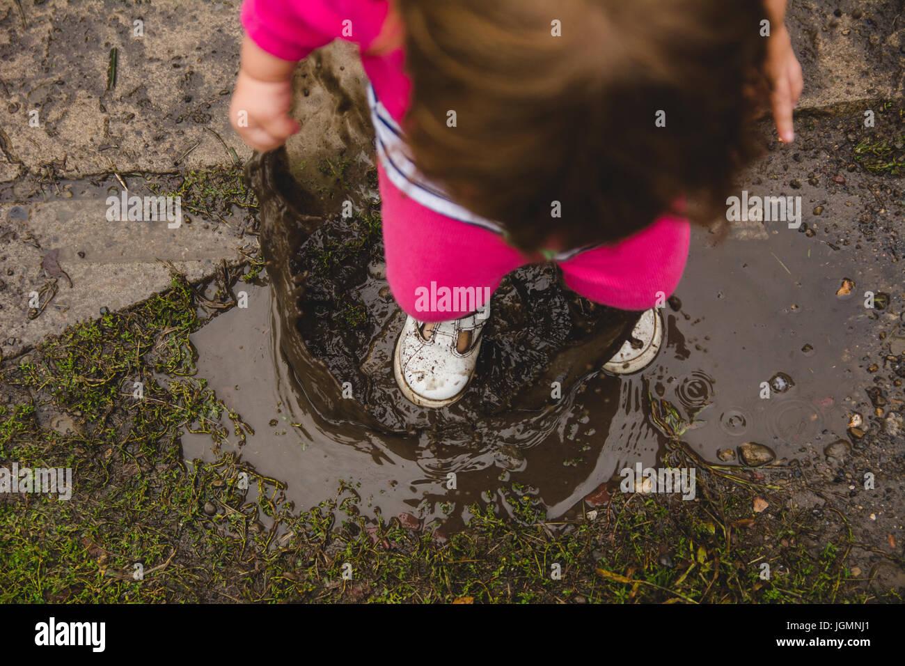 Une fillette de 2 ans en regardant le sol et flaque de boue, des éclaboussures dans une flaque de boue, faisant Photo Stock