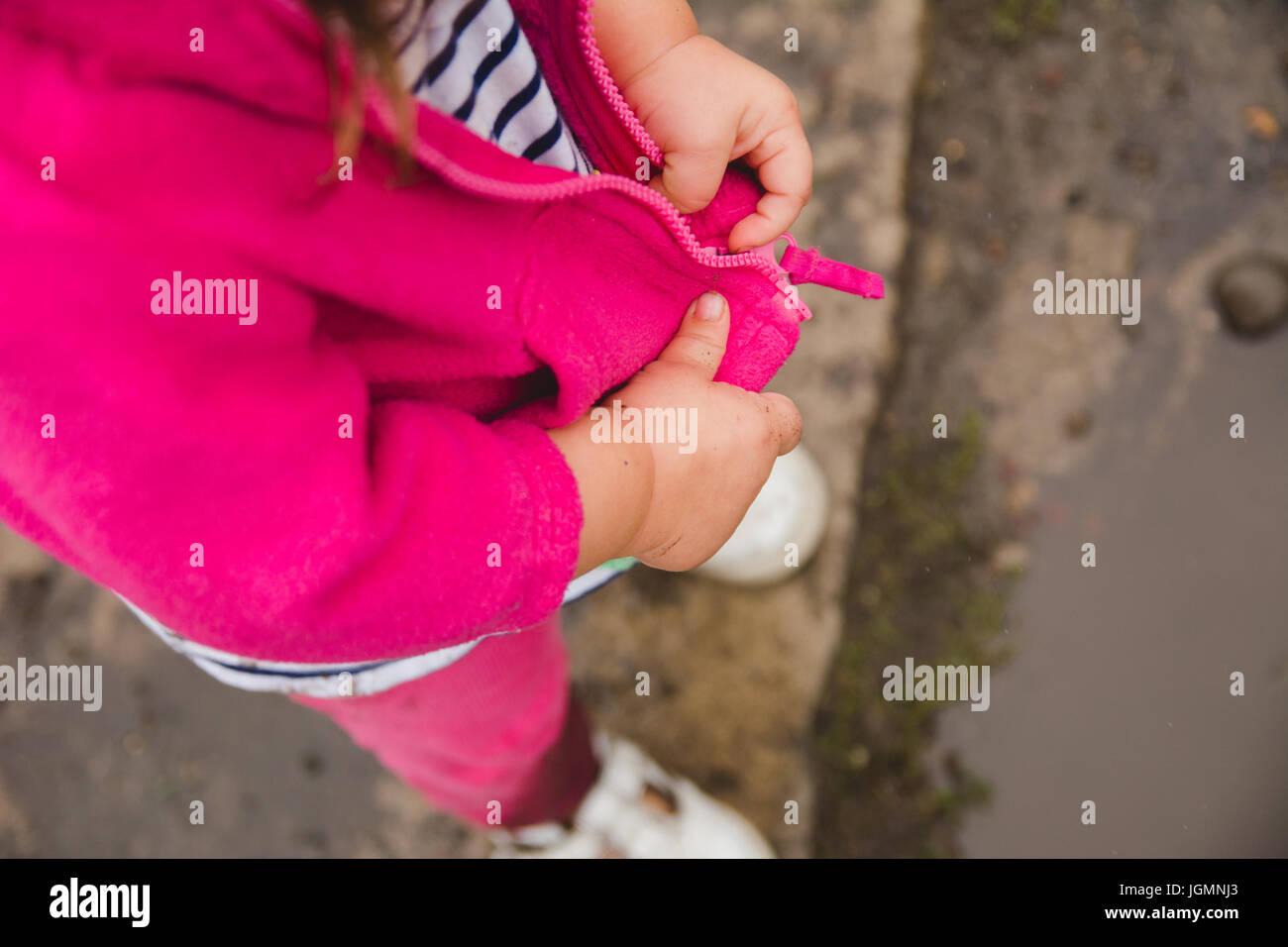 Un bambin zipping son blouson mains seulement. Photo Stock