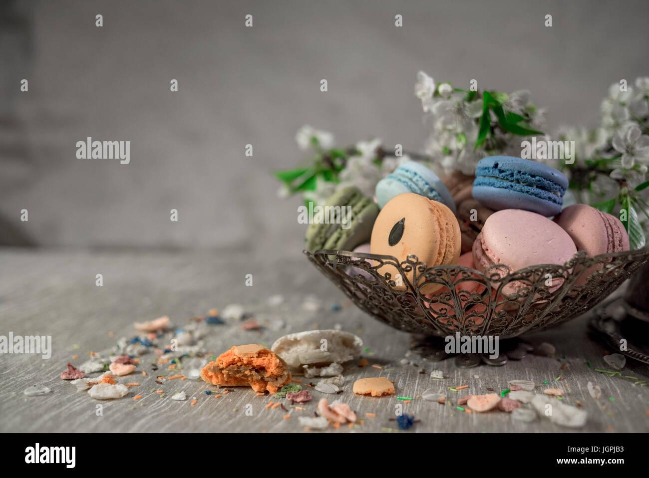 Macarons multicolores sur une table avec l'est de vase et cherry branch en fleurs Photo Stock