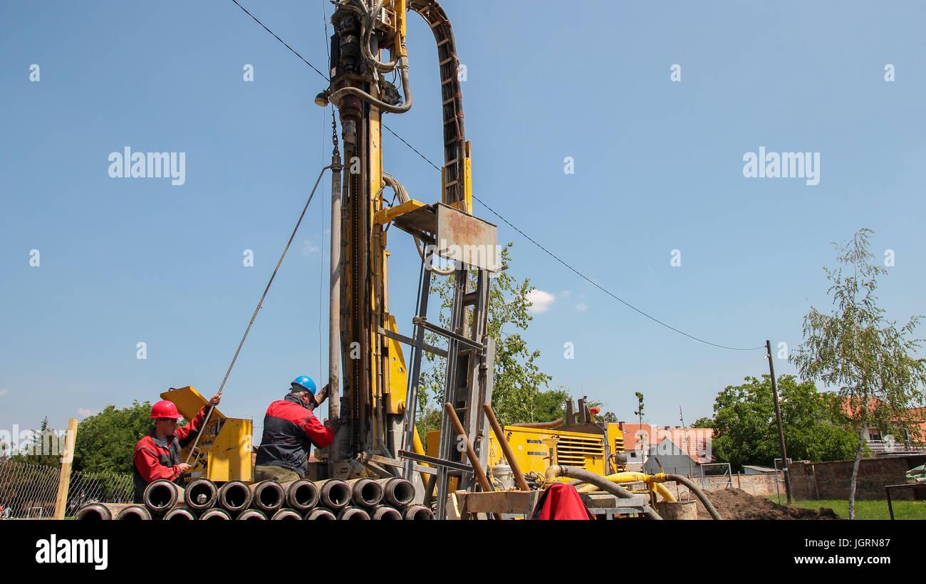 Un travailleur s'apprête à rejoindre deux morceaux de tiges de forage sur une plate-forme de forage. Photo Stock