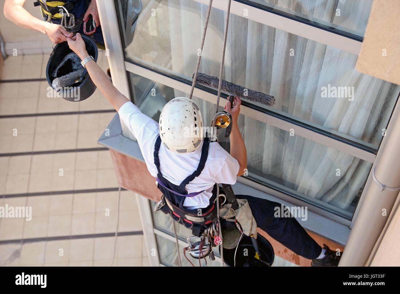 La pendaison des travailleurs sur cordes d'escalade et de travailler ensemble. Photo Stock