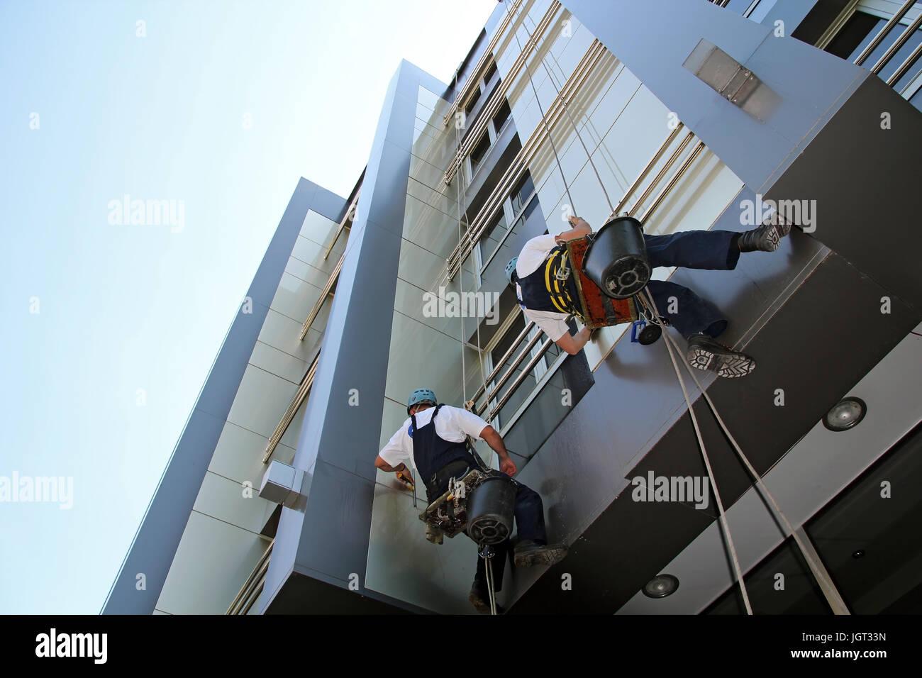 Les travailleurs du nettoyage des vitres façade d'un immeuble de bureaux modernes. Photo Stock