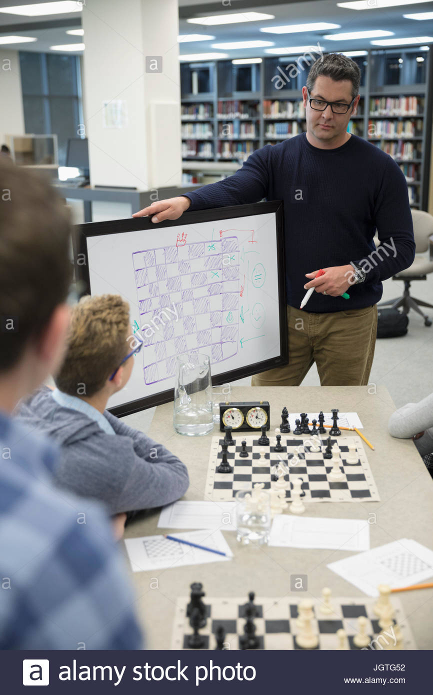 Tableau blanc avec des enseignants menant chess club leçon in library Photo Stock