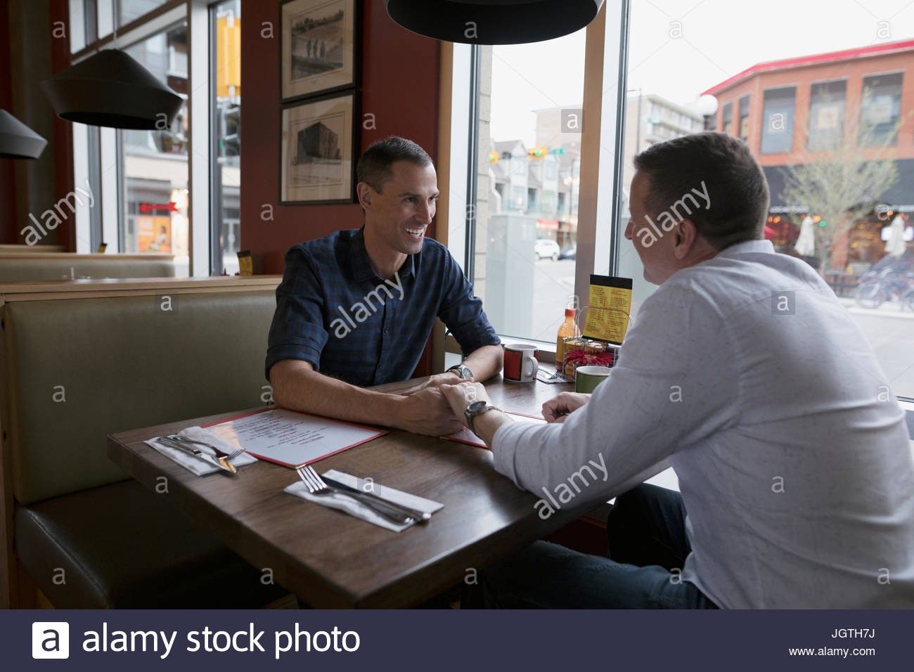 Homme affectueux gay couple holding hands at diner booth Photo Stock
