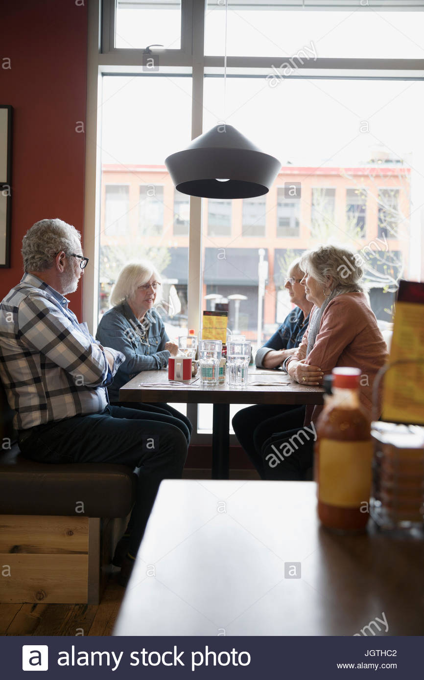 Senior friends dining in diner booth Photo Stock