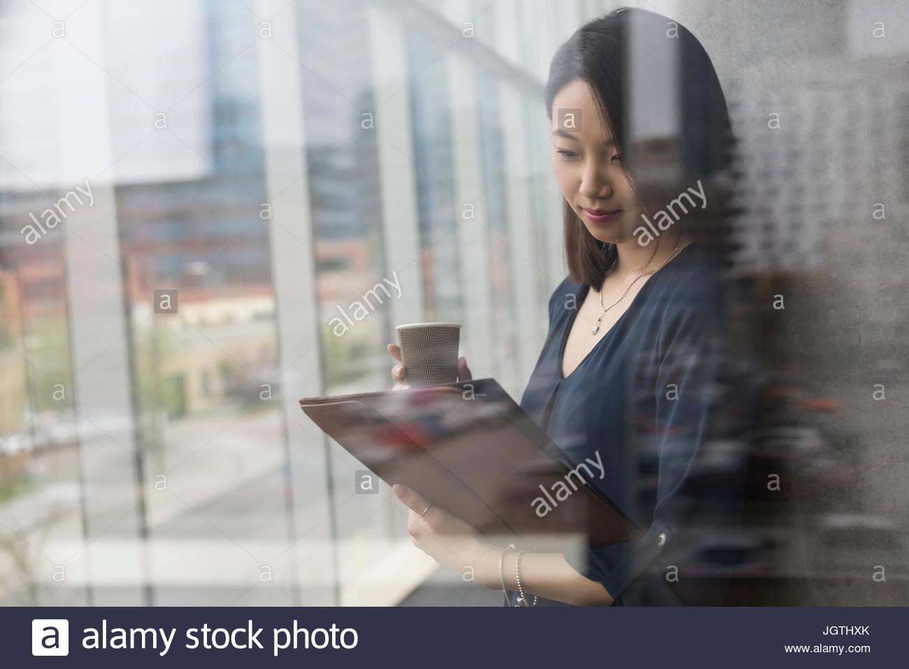 Businesswoman with digital tablet boire espresso dans fenêtre de bureau Photo Stock
