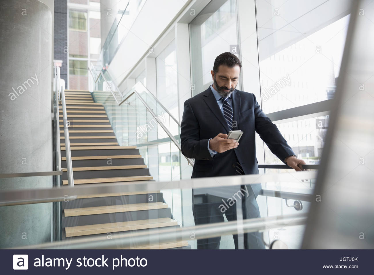 Businessman texting with cell phone on office escaliers Photo Stock