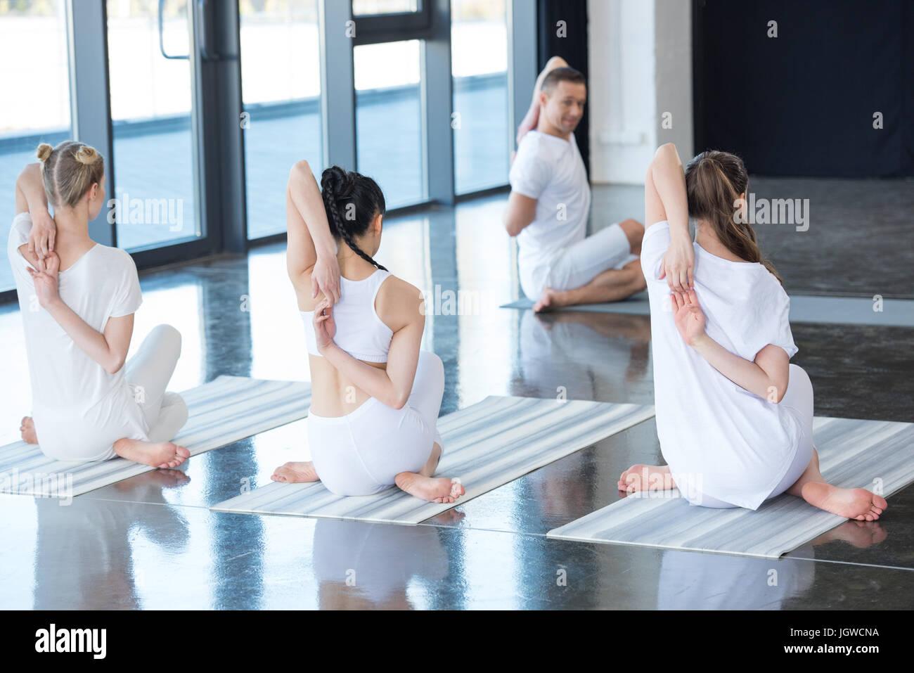 Les femmes et les formateurs Gomukhasana ou vache face à poser sur un tapis de yoga Photo Stock