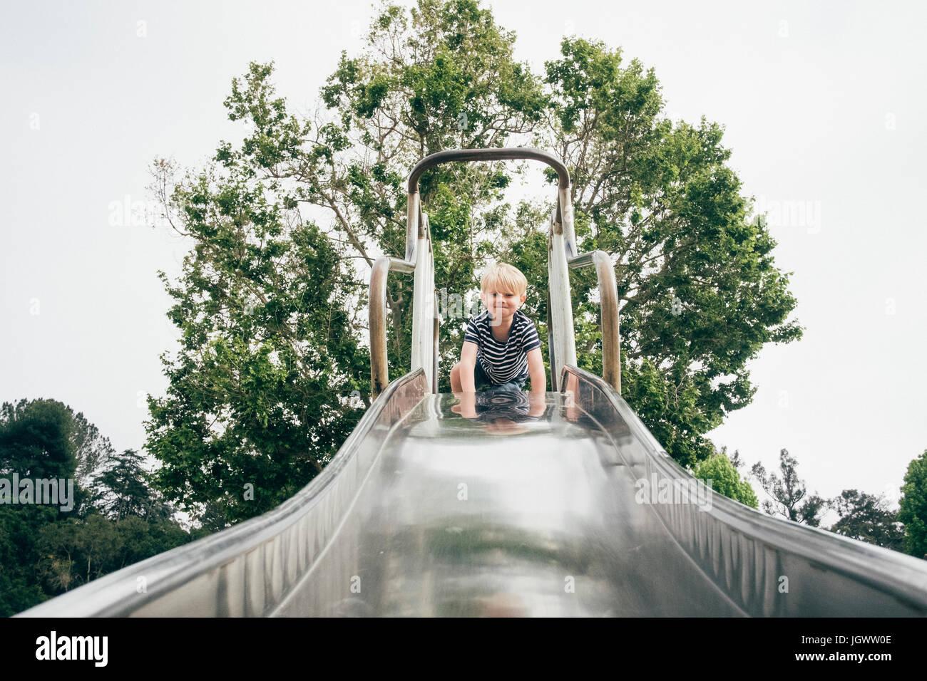 Portrait de jeune garçon en haut de l'aire de glisse, low angle view Photo Stock