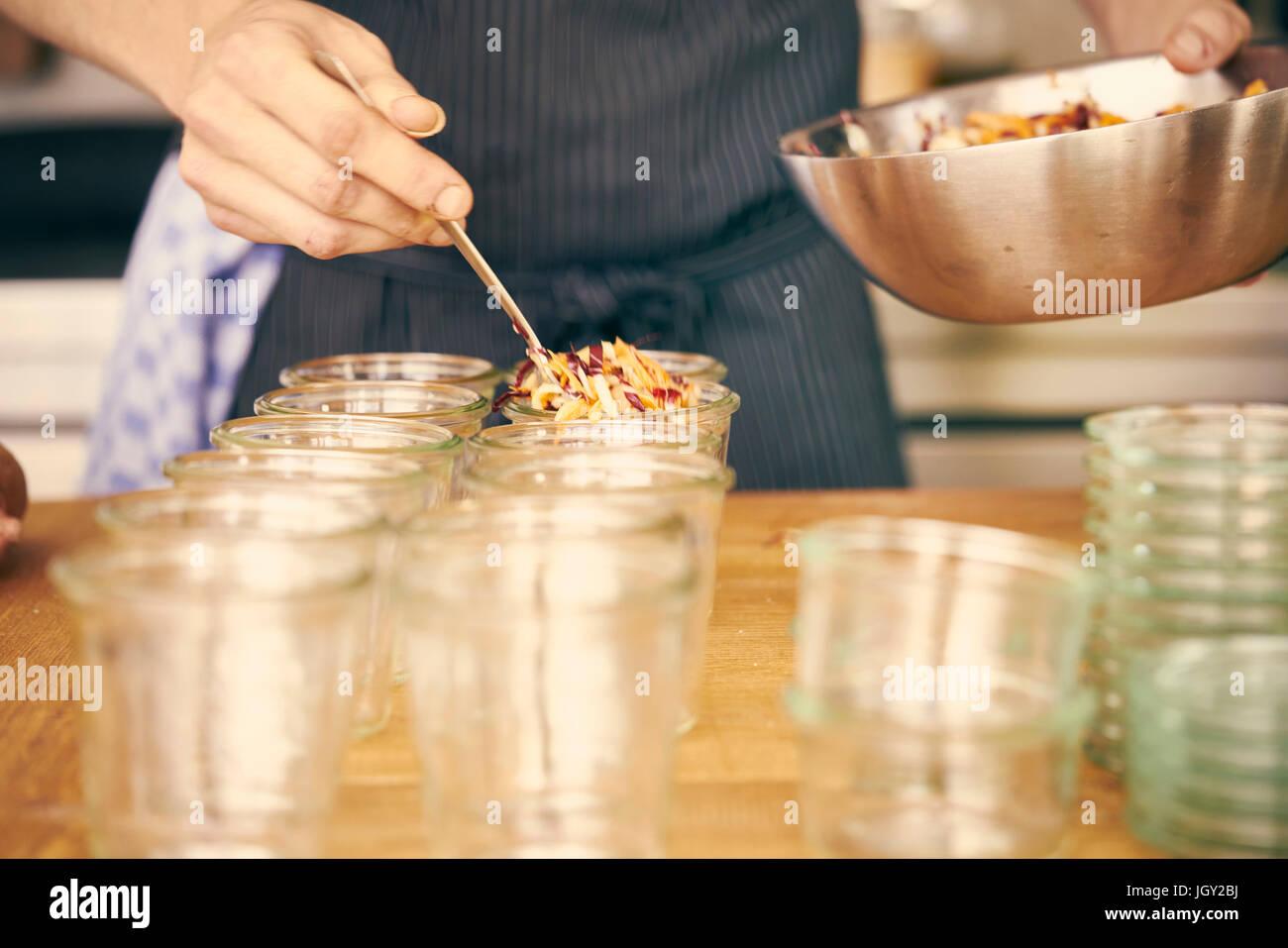 Remplissage des récipients en plastique avec Chef de portions de nourriture Photo Stock
