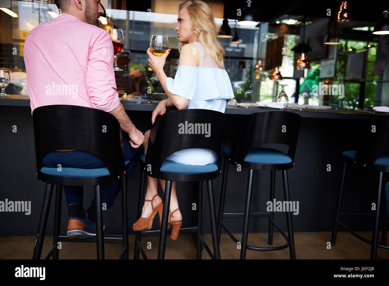 Vue arrière de l'homme de toucher la jeune femme en colère genou à bar Photo Stock