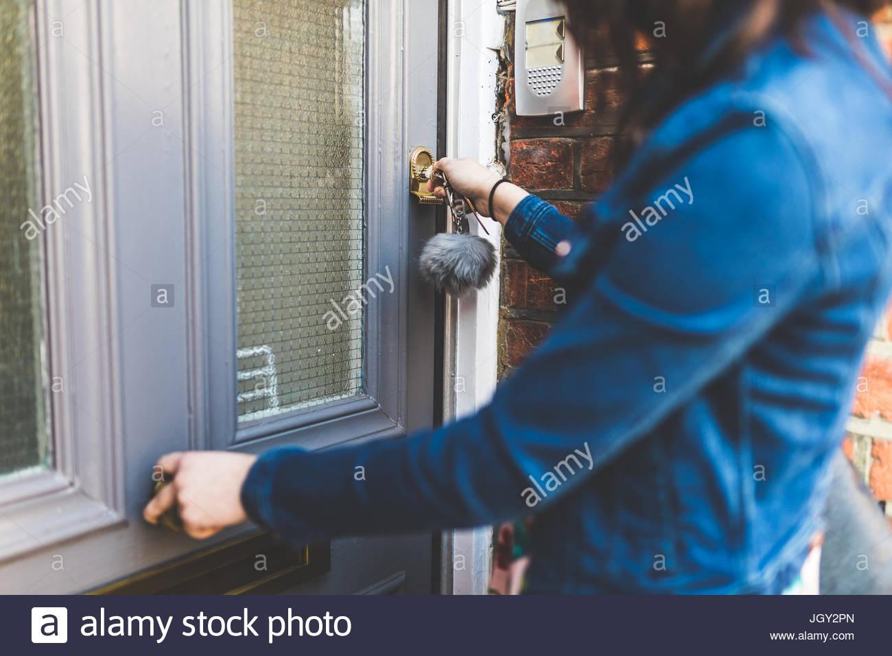Jeune femme laissant house, verrouillage porte avant, mid section Photo Stock