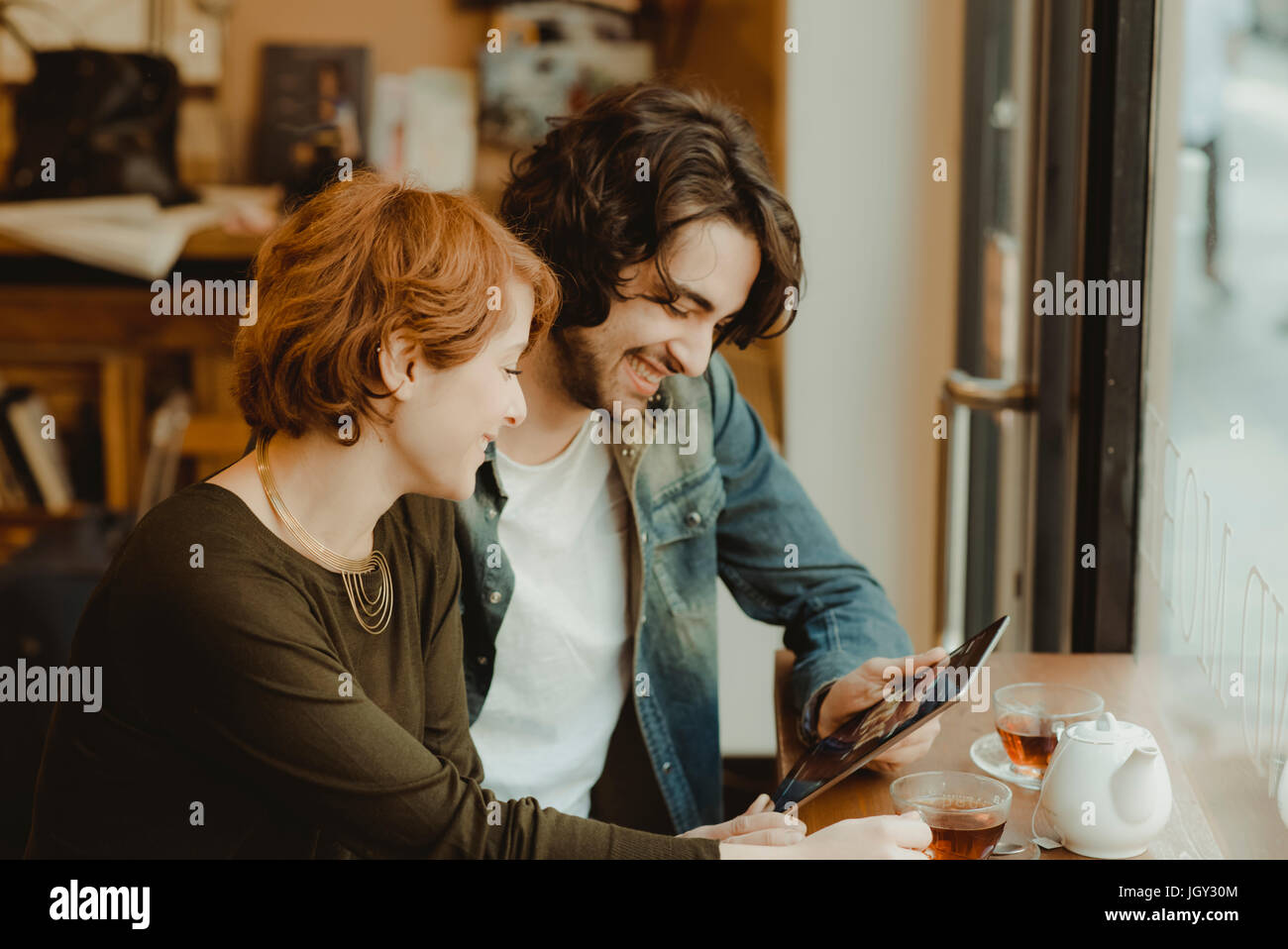 Young couple sitting in cafe, looking at digital tablet Photo Stock