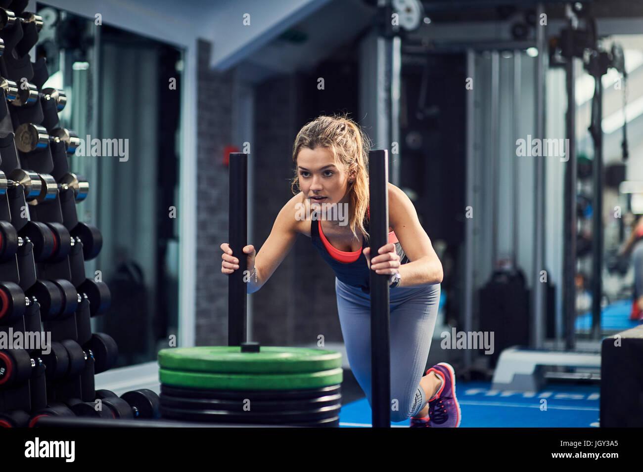 Jeune femme, de formation de poids poussant en traîneau sport Photo Stock