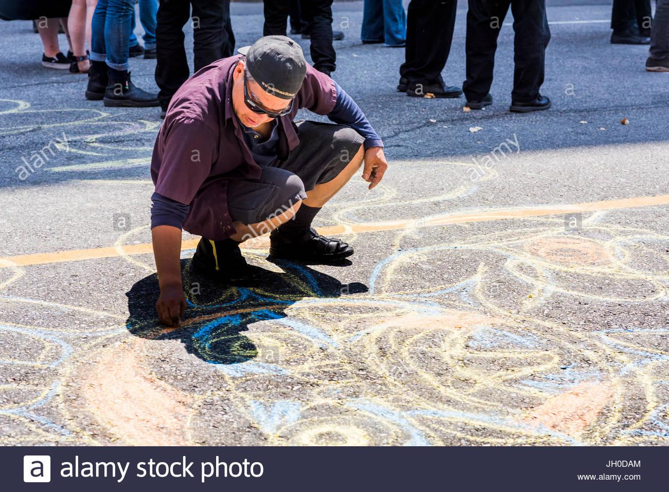 La création d'homme dessin à la craie sur la route. Balmoral Block Party à l'appui de l'expulsé Photo Stock