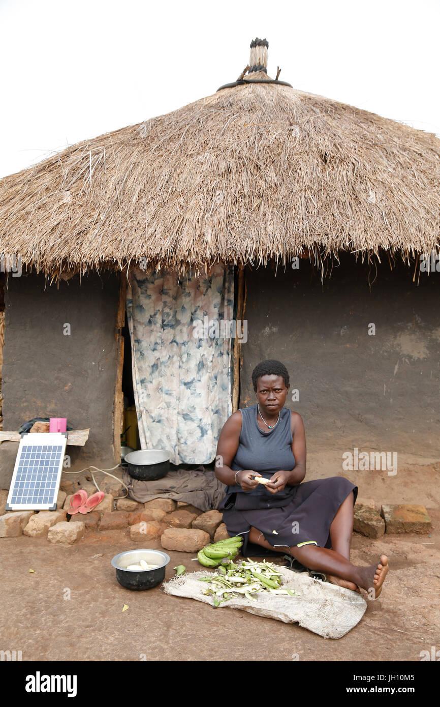 Woman peeling légumes en dehors de sa maison. L'Ouganda. Photo Stock
