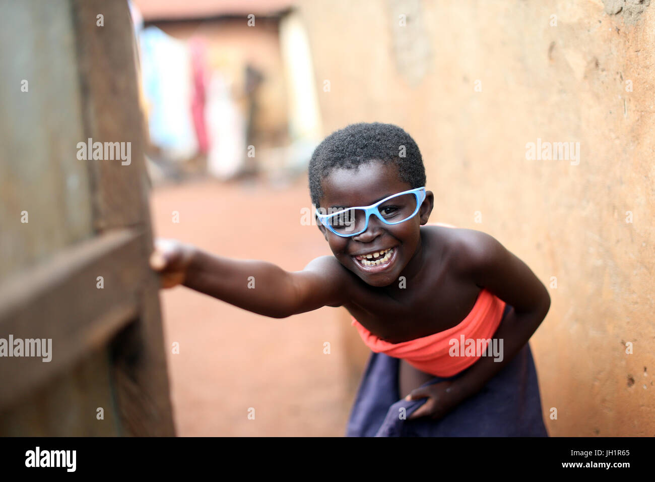Smiling african girl with blue lunettes. Le Togo. Photo Stock
