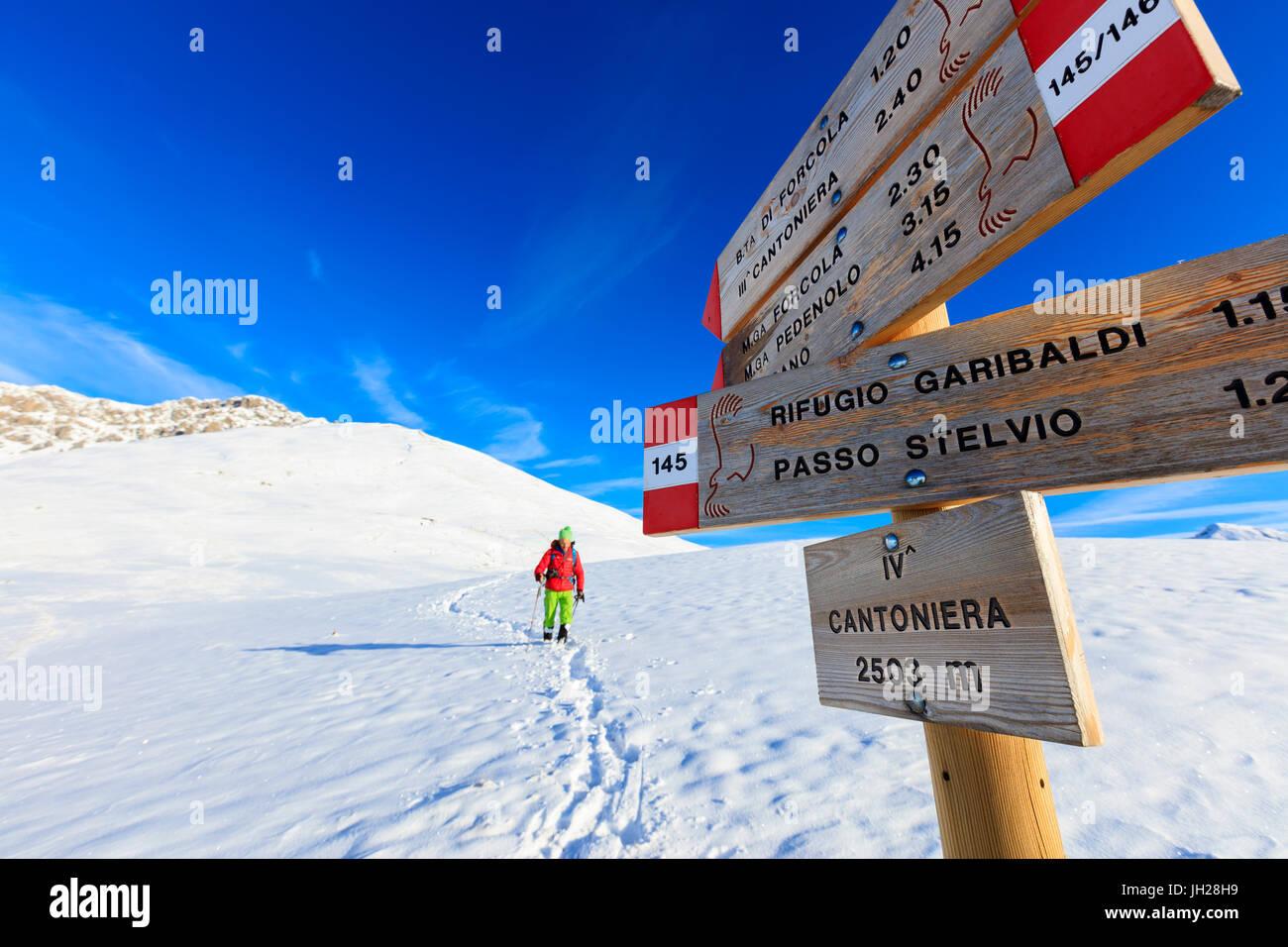 Randonneur avec le produit sur le chemin couvert de neige, la vallée de la Valteline, Braulio, Lombardie, Italie, Photo Stock