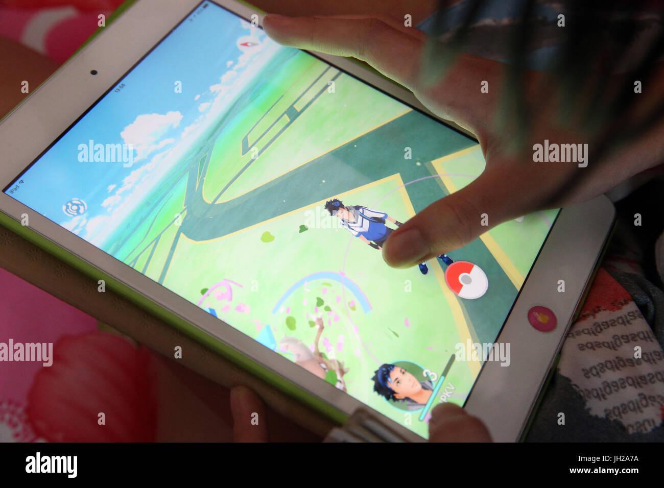 Fille jouant avec son comprimé pendant un Pokemon Rendez gaming. Ho Chi Minh Ville. Le Vietnam. Photo Stock