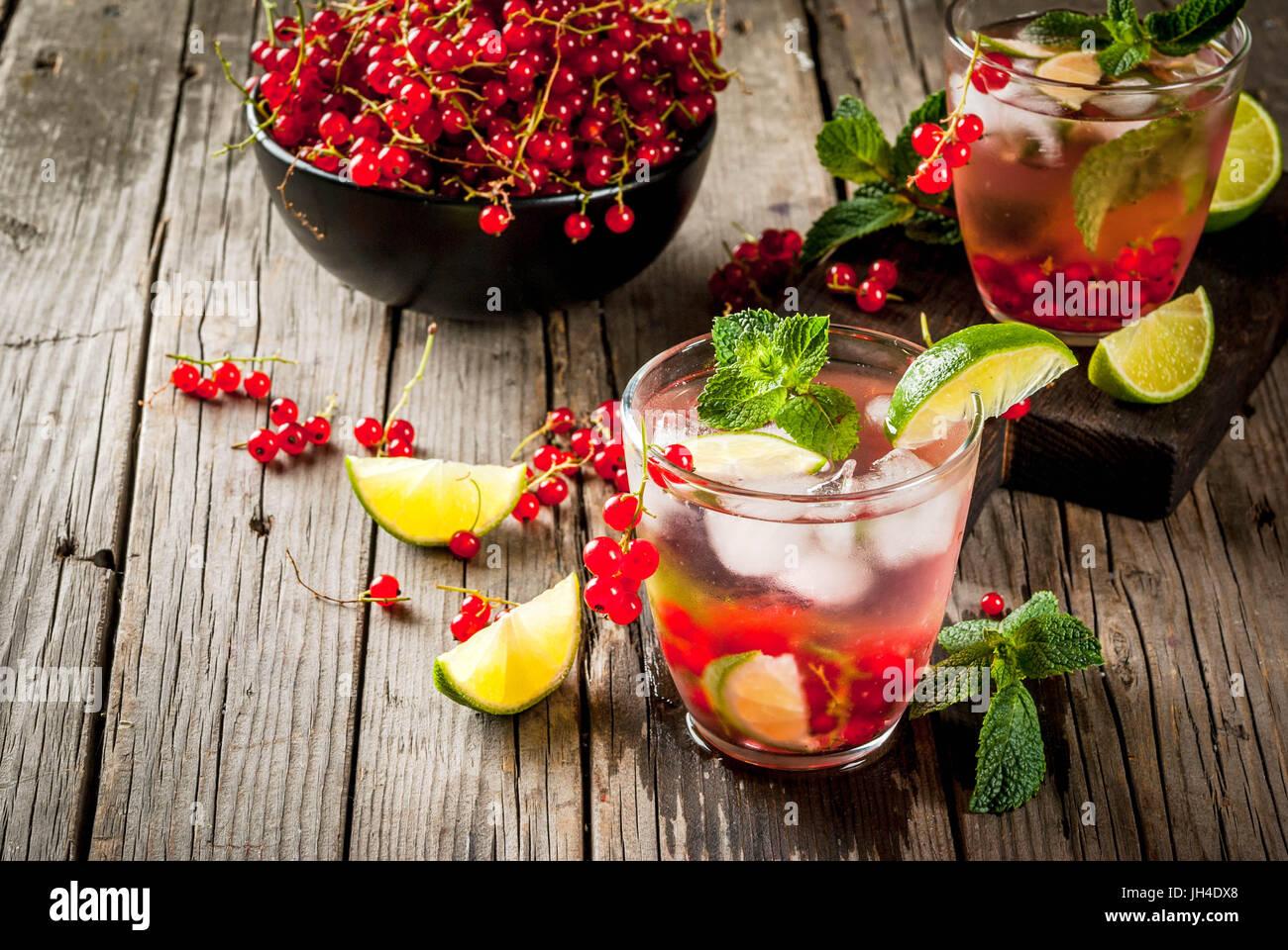 Idées de boissons d'été, des cocktails sains. Le Mojito de lime, menthe et de groseille rouge. Sur la vieille table en bois rustique, avec les ingrédients. Copie Banque D'Images
