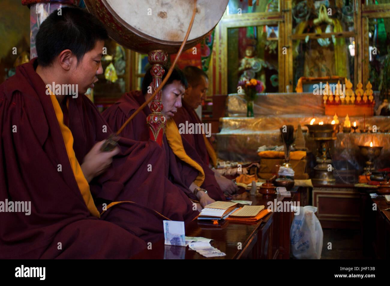 Moines priant à l'intérieur du monastère de Tsepak Lhakhang, Lhassa, Tibet. Photo Stock