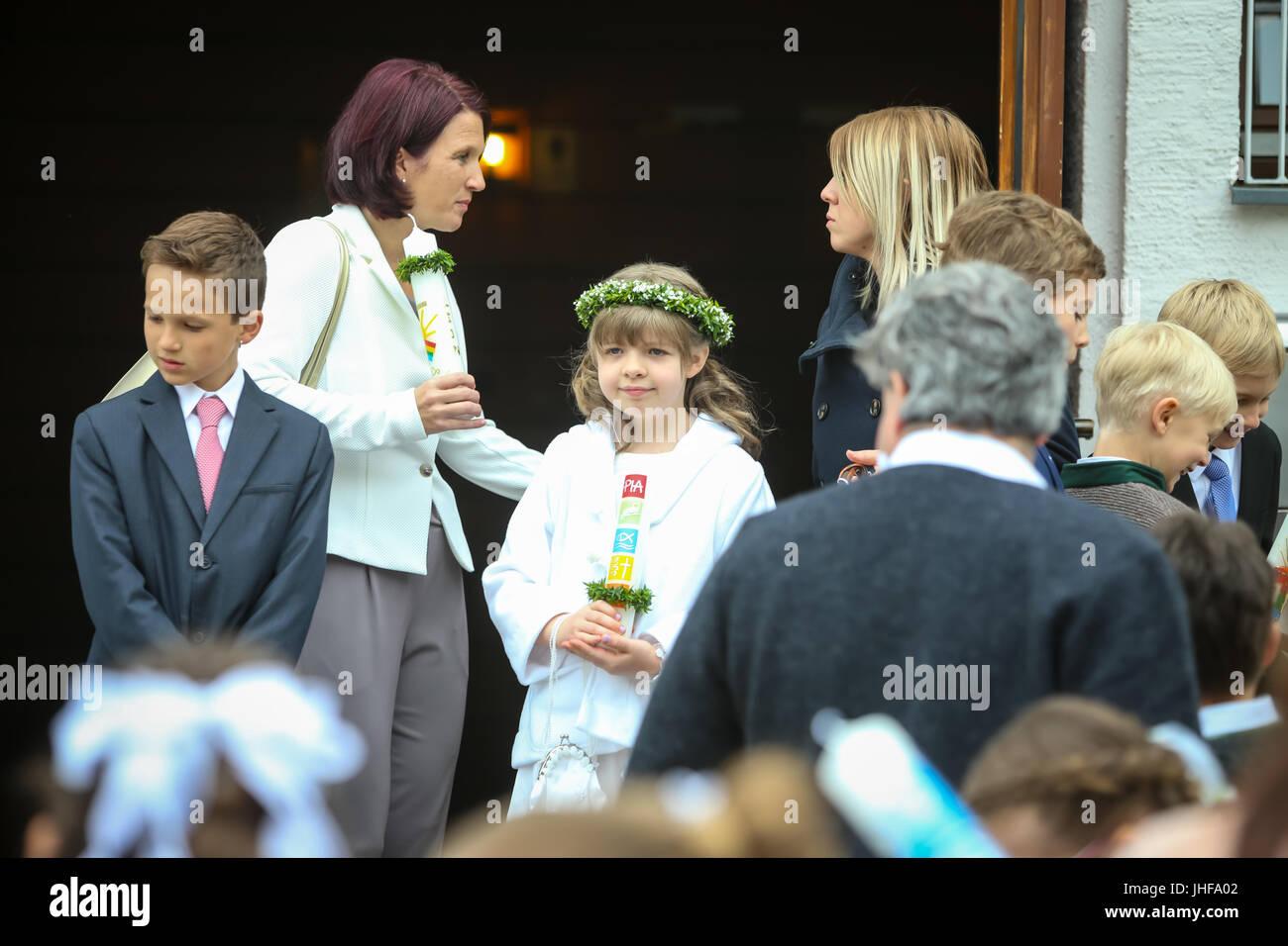 NANDLSTADT, ALLEMAGNE - le 7 mai 2017: Une jeune fille avec une bougie et des adultes debout devant l'église à Banque D'Images