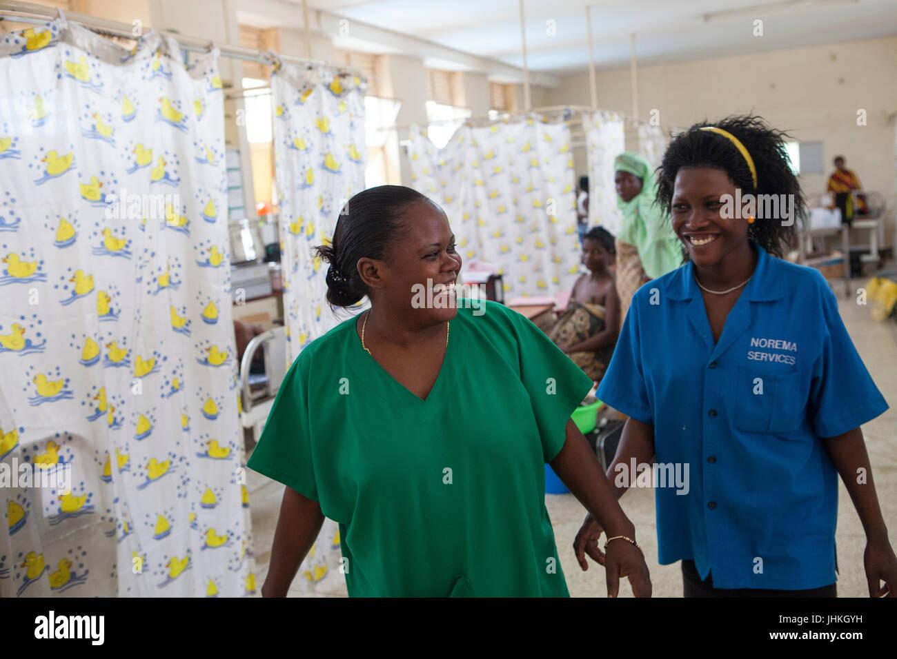Une infirmière et une sage-femme sourire à l'autre pendant une longue période le la maternité Photo Stock