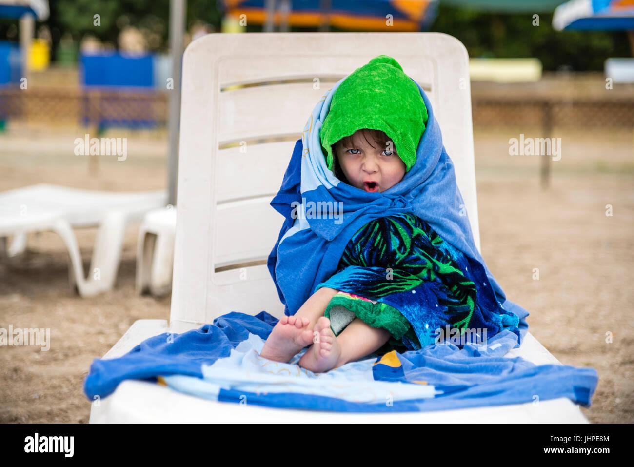 La petite fille enveloppés dans des serviettes pour le réchauffement, les émotions du visage Photo Stock