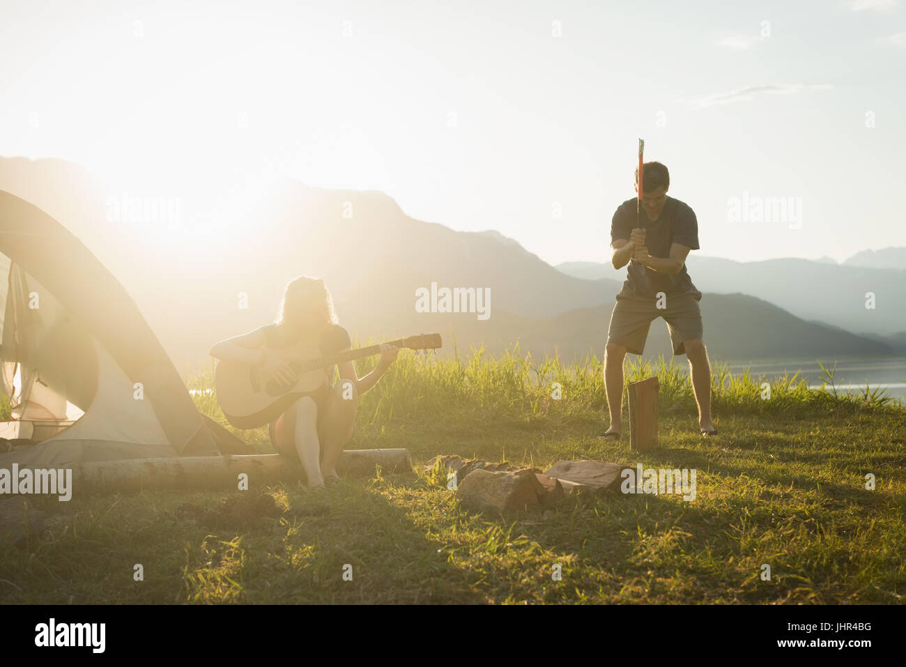 Femme jouant de la guitare tandis que l'homme au journal le fractionnement du camping Photo Stock