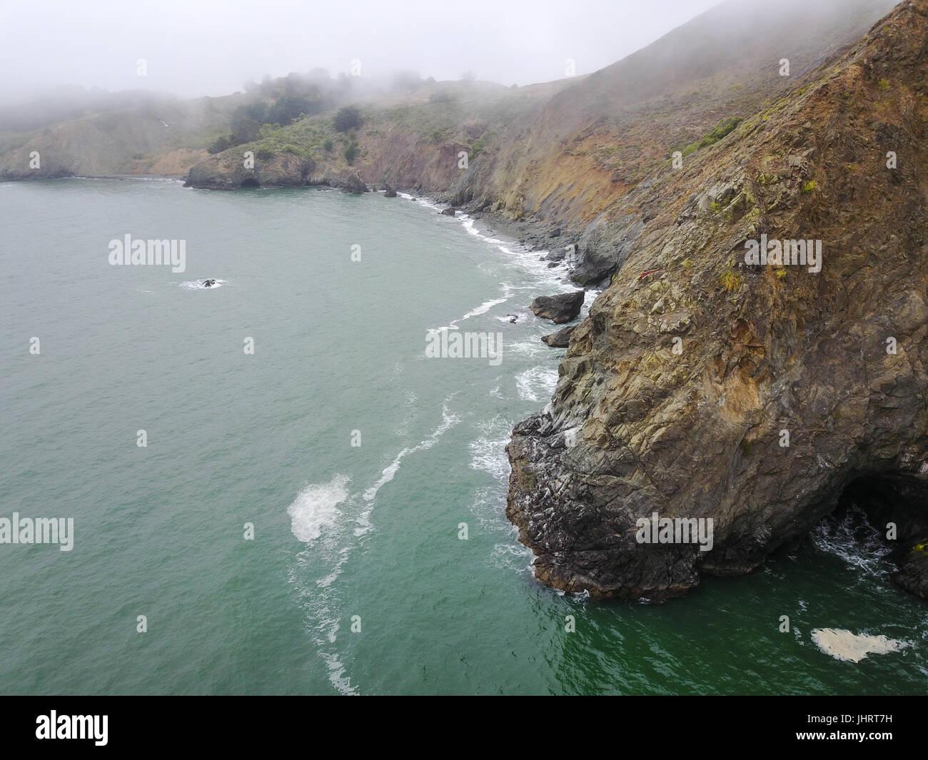 Les eaux froides de l'océan Pacifique se lave à l'encontre de la côte couverte de brouillard Photo Stock