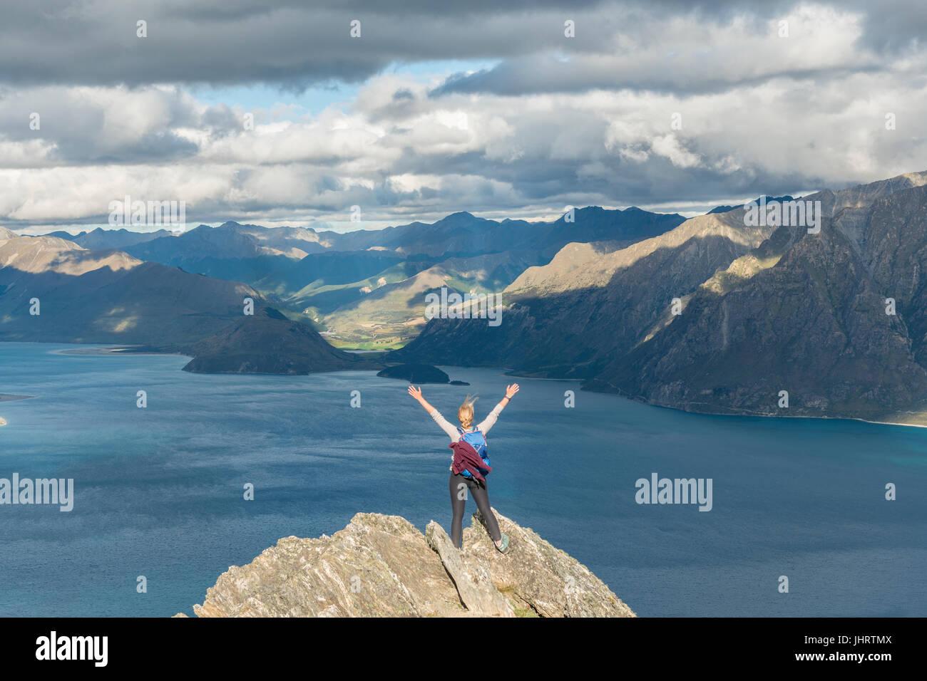 Female hiker sur un rocher, s'étirant les bras en l'air, le lac Hawea et paysage de montagne, Pic isthme, Photo Stock