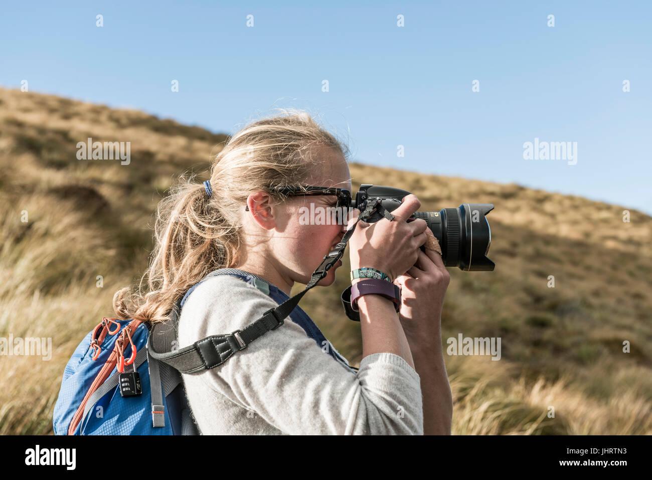Female hiker prendre photo avec un appareil photo reflex, Otago, île du Sud, Nouvelle-Zélande Photo Stock