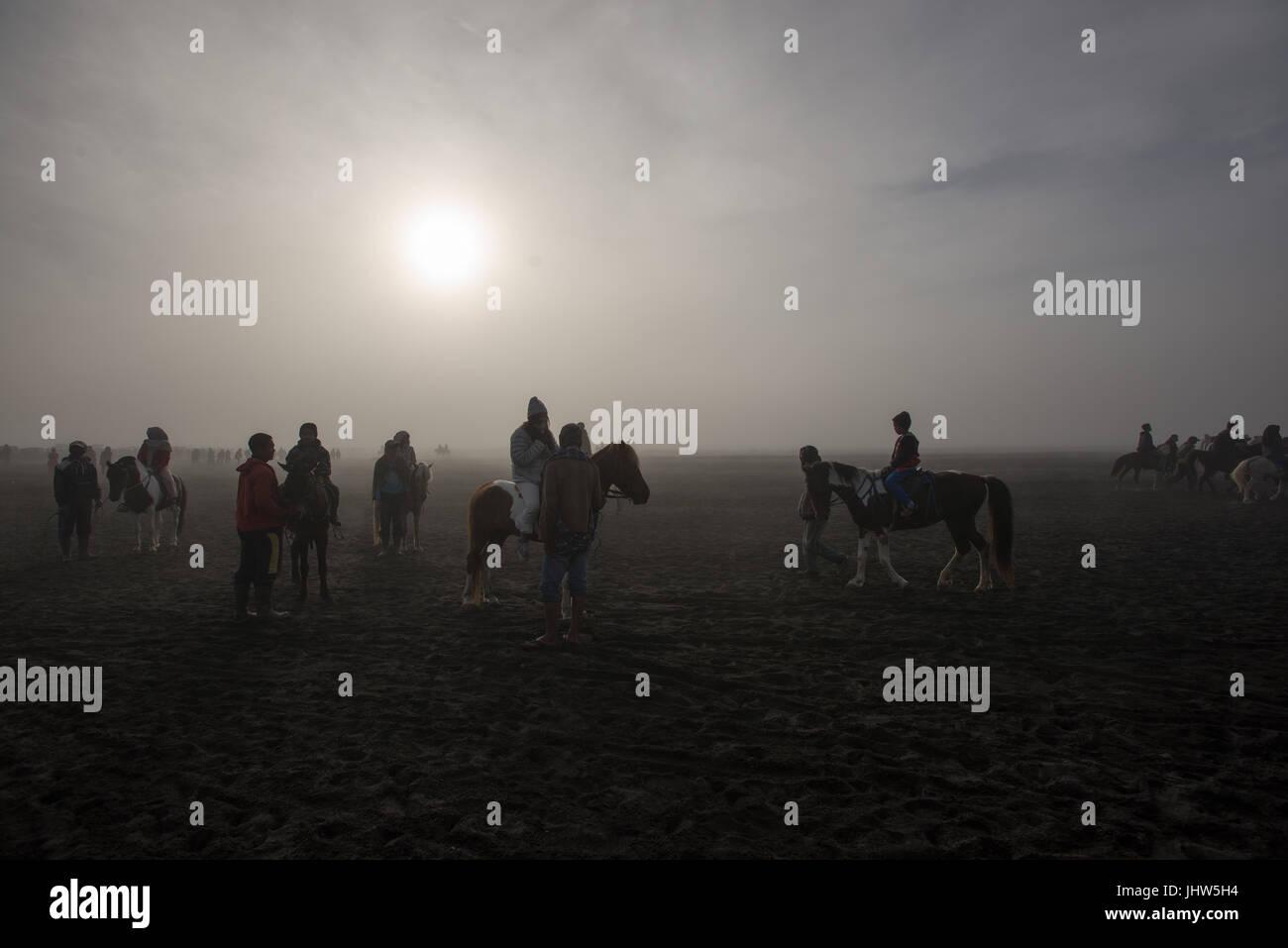 Les Indonésiens l'équitation dans une mer de sable dans le Mont Bromo est de Java en Indonésie. Photo Stock