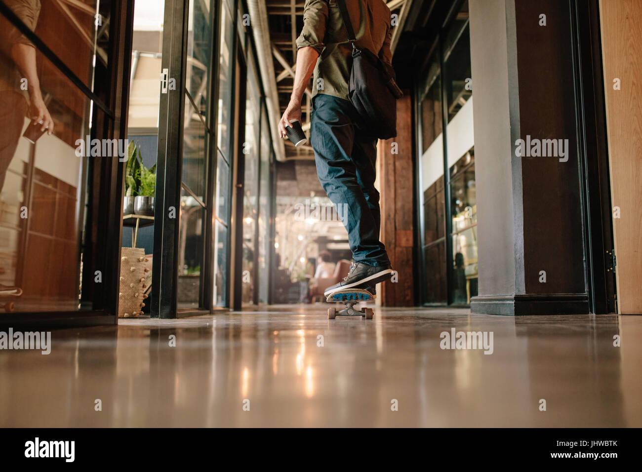 Vue arrière de l'angle faible shot of casual man skateboarding in office. Jeune homme d'affaires par Photo Stock