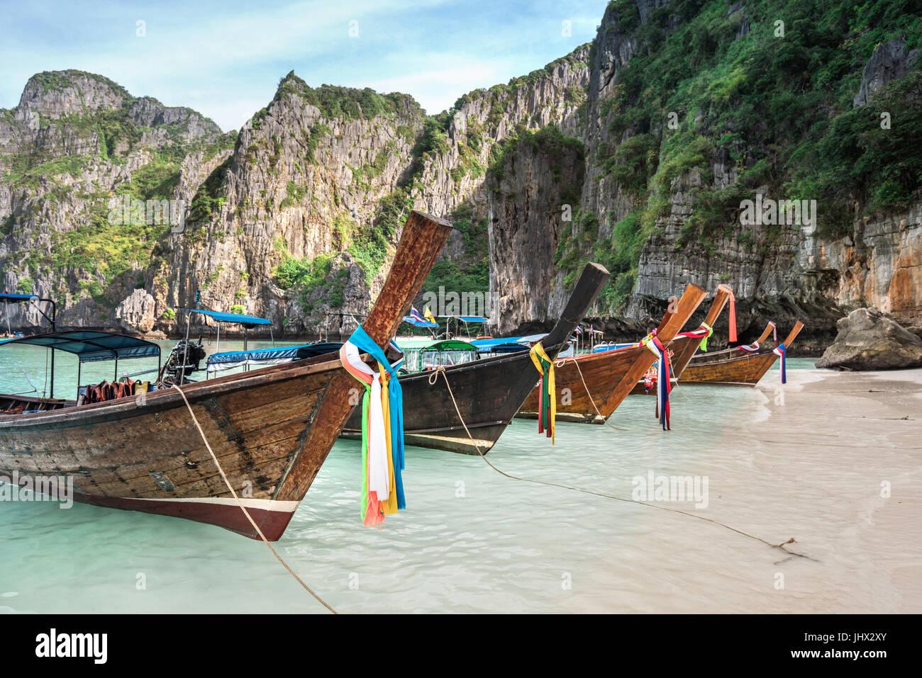 La Thaïlande vue mer plage rond avec des collines calcaires avec de nombreux bateaux longtail traditionnels Photo Stock