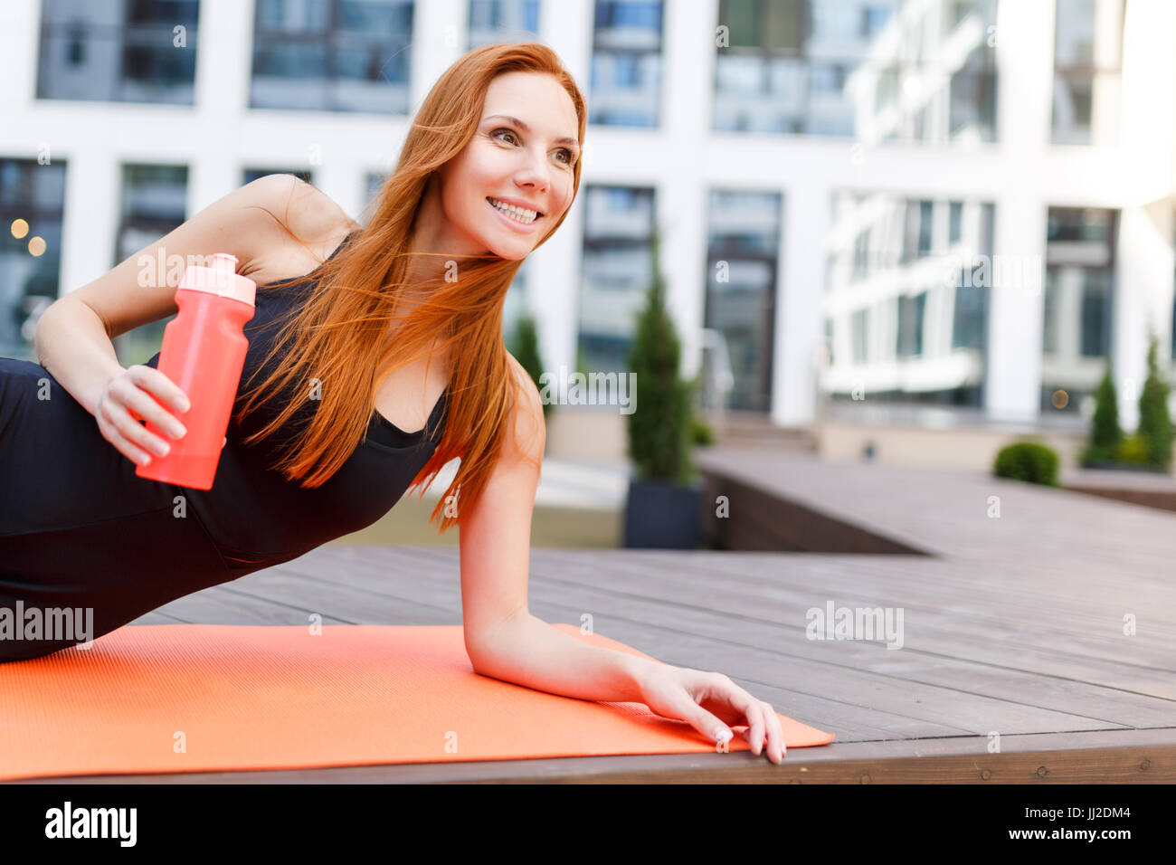 Sportswoman doing exercises on rug Banque D'Images