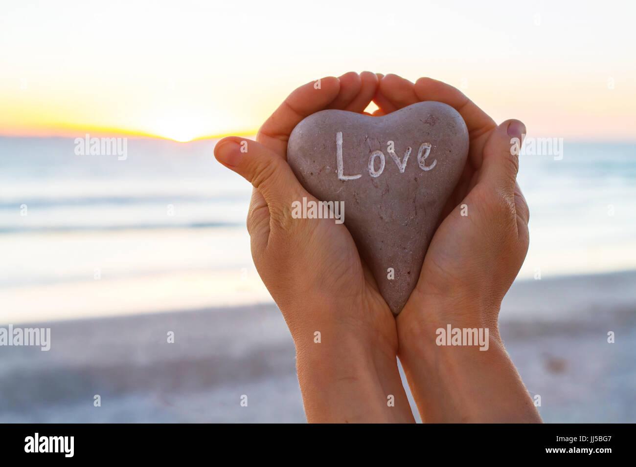Concept d'amour, mains tenant coeur de sunset beach Photo Stock